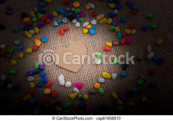 Paper heart amid pebbles on canvas ground - csp61956910