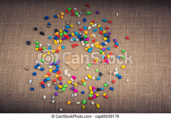 Paper heart amid pebbles on canvas ground - csp65039176