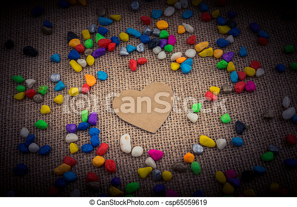 Paper heart amid pebbles on canvas ground - csp65059619