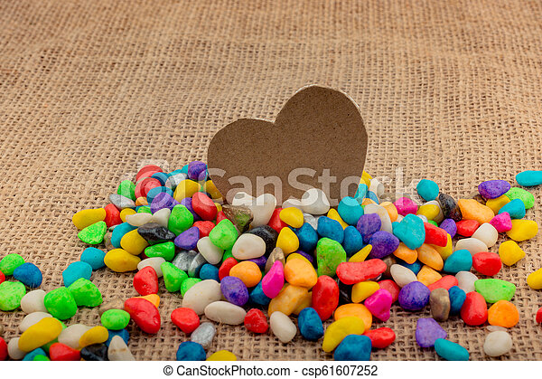 Paper heart amid pebbles on canvas ground - csp61607252