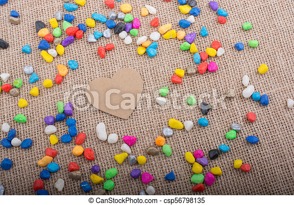 Paper heart amid pebbles on canvas ground - csp56798135