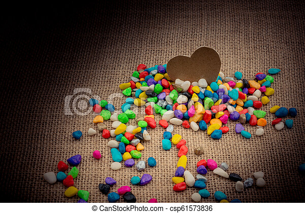 Paper heart amid pebbles on canvas ground - csp61573836
