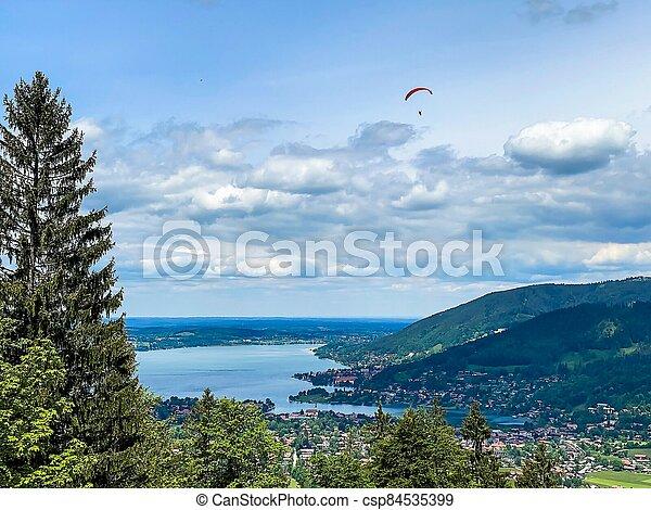 Paraglider flying over the lake. Paragliding under Bavarien landscape - csp84535399