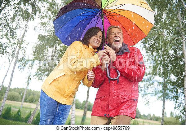 Una pareja húmeda escondida bajo un paraguas colorido - csp49853769
