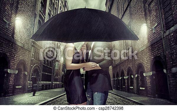 Una pareja joven escondida bajo el paraguas - csp28742398