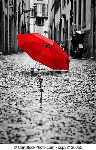 Un paraguas rojo en la calle Cobblestone en la vieja ciudad. Viento y lluvia - csp32130055