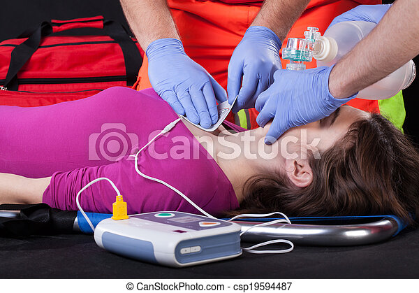Paramedics using defibrillator on a patient - csp19594487