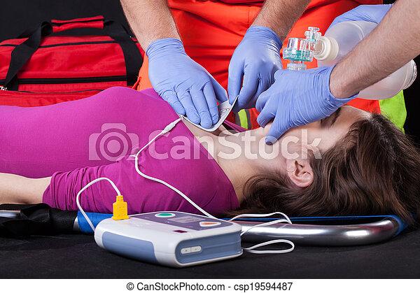 Paramedics using defibrillator on a patient - csp19594487