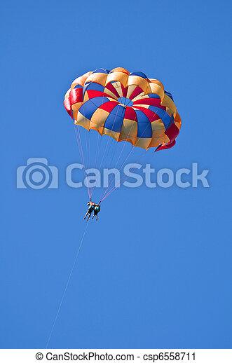 Parasailing under blue sky. - csp6558711