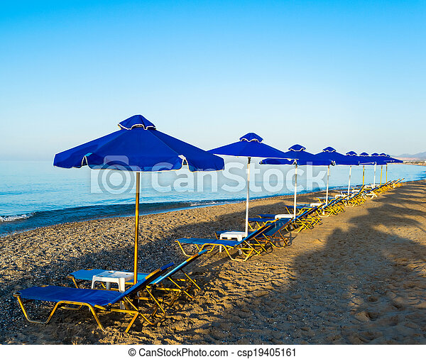 Parasols and chais-longue on the beach - csp19405161