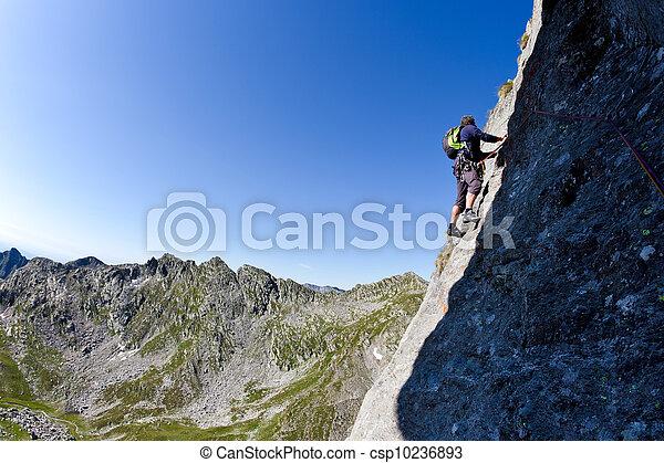 Escalador caucásico escalando una pared empinada - csp10236893