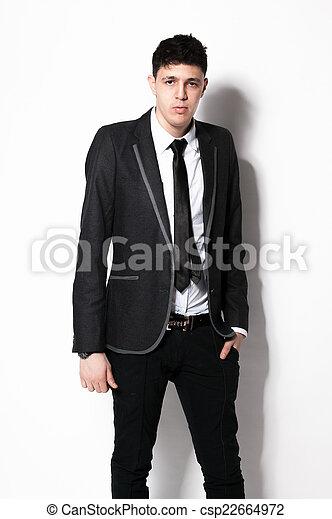 Elegante en traje negro apoyado contra la pared blanca en el estudio - csp22664972