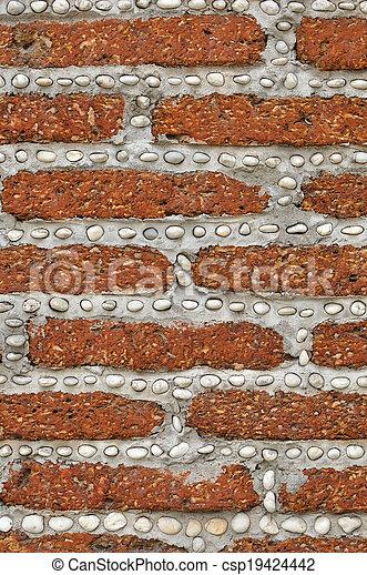 Un muro de ladrillo rojo con pequeñas rocas blancas. - csp19424442