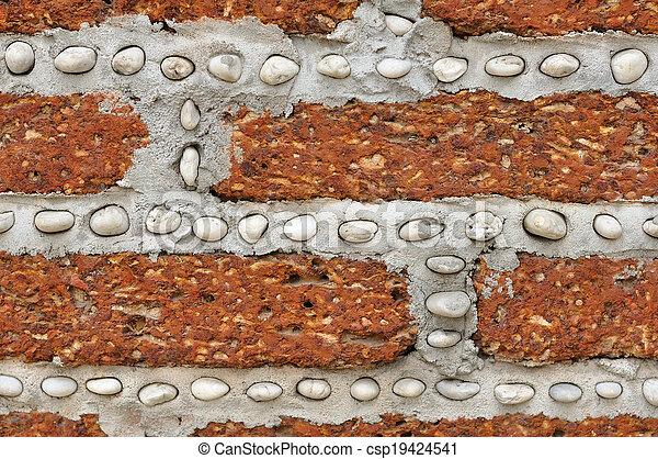 Un muro de ladrillo rojo con pequeñas rocas blancas. - csp19424541