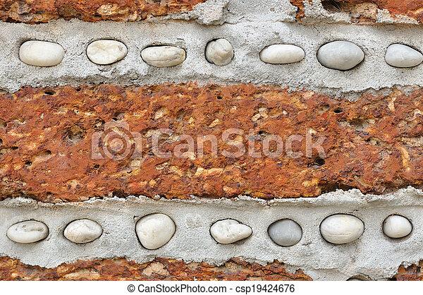 Un muro de ladrillo rojo con pequeñas rocas blancas. - csp19424676