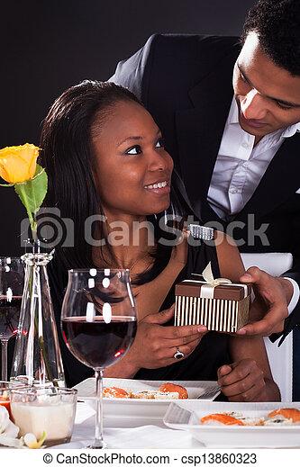 Una pareja africana con un regalo en las manos - csp13860323