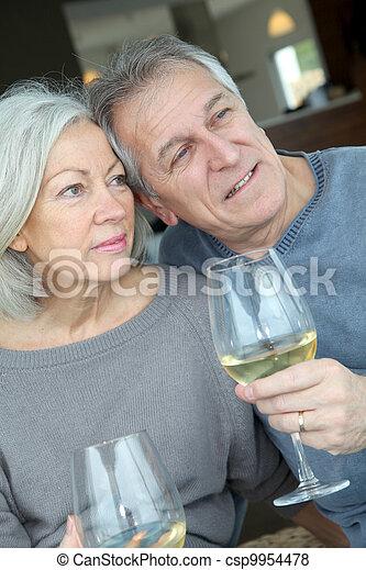 Retrato de feliz pareja de ancianos vitoreando con vino - csp9954478