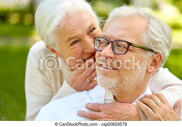 Cerca de una pareja mayor susurrando al aire libre - csp50624579