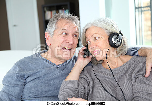 La pareja mayor escucha música con auriculares - csp9956693