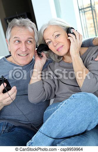 La pareja mayor escucha música con auriculares - csp9959964