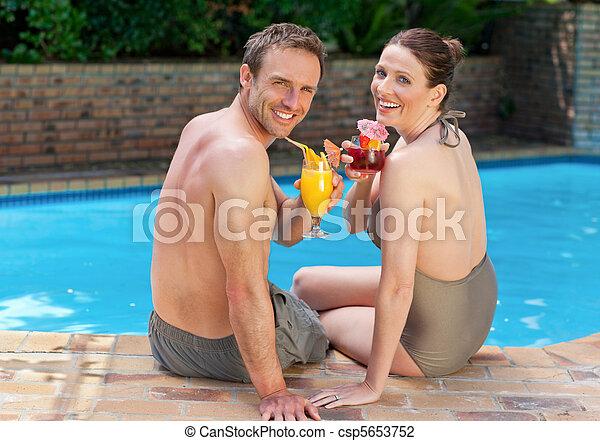Una pareja feliz bebiendo cócteles - csp5653752