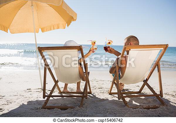 Una pareja feliz bebiendo cócteles mientras se relajan en sus sillas de cubierta - csp15406742