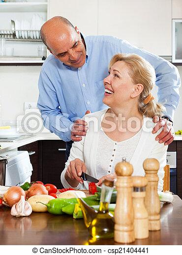 Una pareja mayor cocinando juntos en la cocina - csp21404441