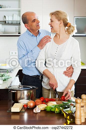 Una pareja mayor cocinando ensalada - csp27442272