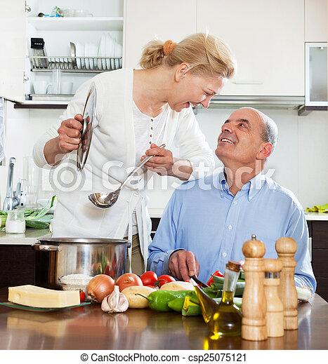Sonriente pareja de ancianos y cocinar juntos en la cocina - csp25075121