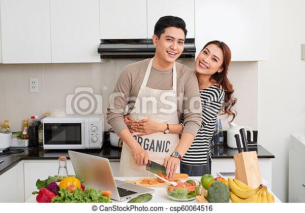 Una pareja encantadora cocinando juntos en la cocina en casa - csp60064516