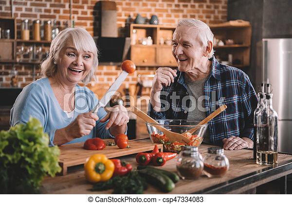 Una feliz pareja de ancianos cocinando juntos y divirtiéndose en la cocina - csp47334083