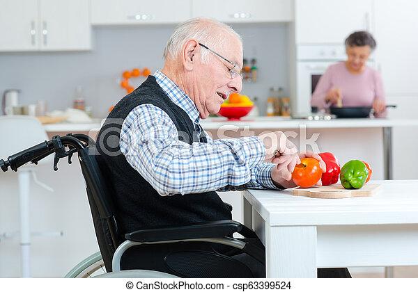 Una pareja mayor cocinando juntos, un hombre discapacitado en silla de ruedas - csp63399524