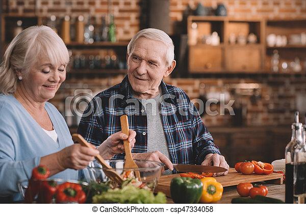 Retrato de feliz pareja senior cocinando juntos en casa - csp47334058