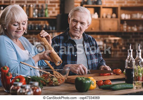 Retrato de feliz pareja senior cocinando juntos en casa - csp47334069