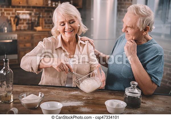 Una pareja sonriente cocinando juntos en la mesa de la cocina - csp47334101