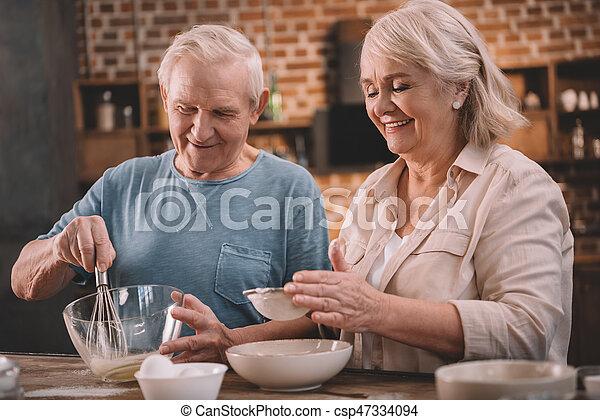 Una pareja sonriente cocinando juntos en la mesa de la cocina - csp47334094