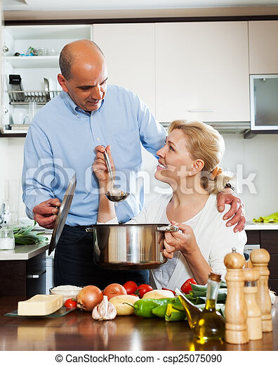 Una pareja mayor cocinando verduras - csp25075090