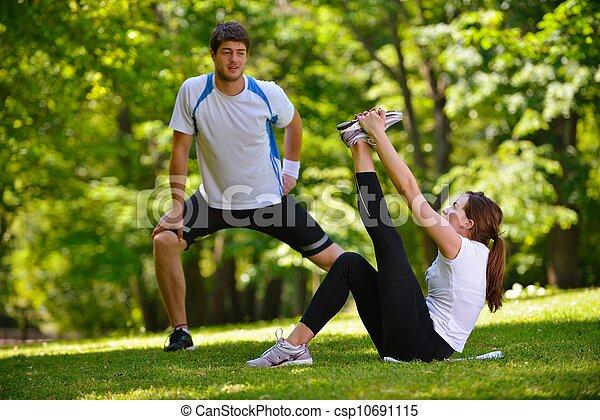 Una pareja haciendo ejercicio de estiramiento después de correr - csp10691115