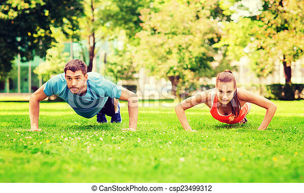 Una pareja haciendo flexiones al aire libre - csp23499312