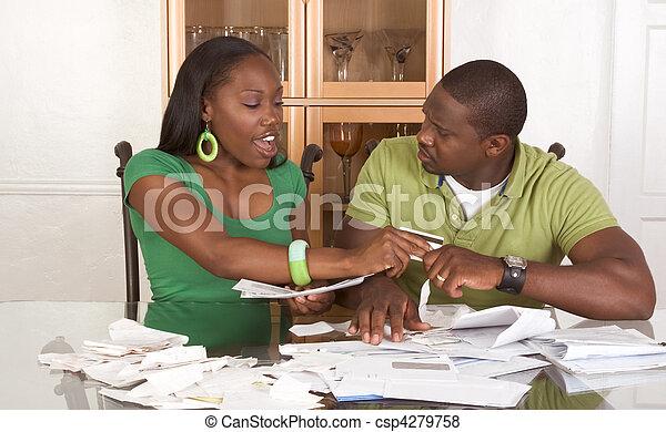 Jóvenes parejas étnicas por mesa llenas de facturas - csp4279758