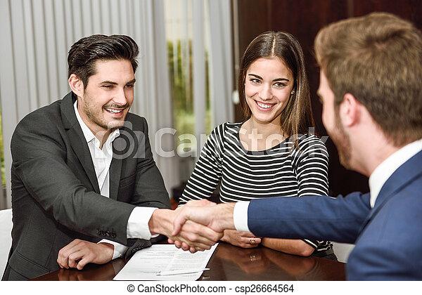 Una joven pareja sonriente estrechando la mano con un agente de seguros - csp26664564