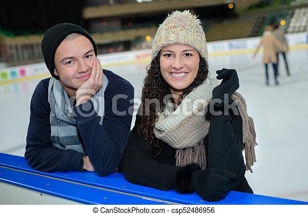Retrato de parejas jóvenes al lado de la pista de hielo - csp52486956