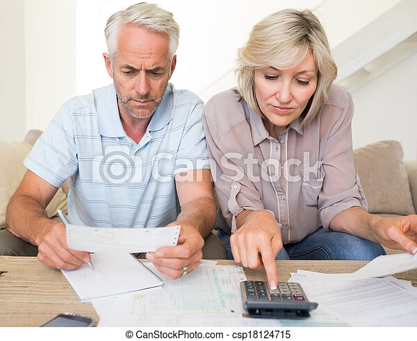 Una pareja madura concentrada con cuentas y calculadora en casa - csp18124715