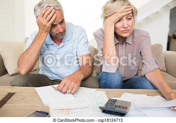 Una pareja madura tensa con cuentas y calculadora en casa - csp18124713