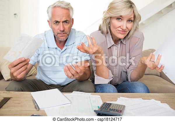 Una pareja madura tensa con cuentas y calculadora en casa - csp18124717