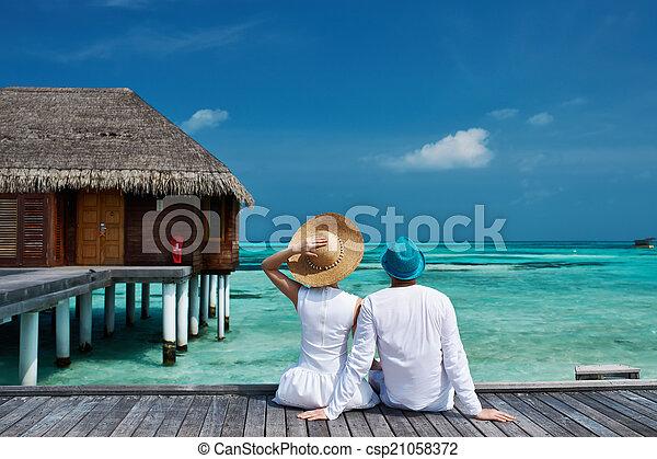Una pareja en un embarcadero en Maldivas - csp21058372