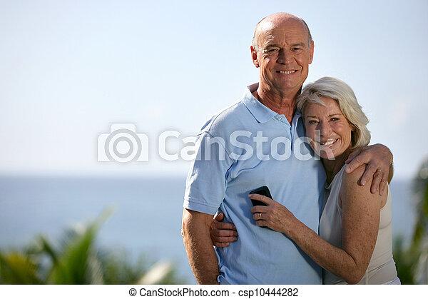 Una pareja mayor abrazándose al aire libre - csp10444282
