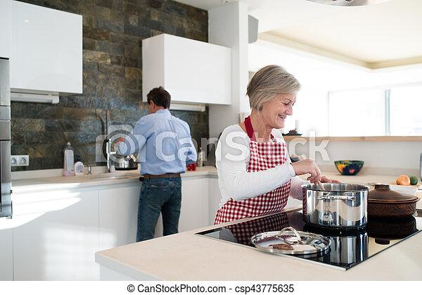 Una pareja mayor en la cocina cocinando juntos. - csp43775635