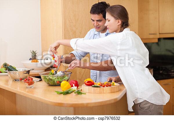 Una pareja feliz preparando una ensalada - csp7976532