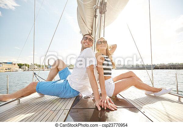 Pareja sonriente sentada en la cubierta de yates - csp23770954